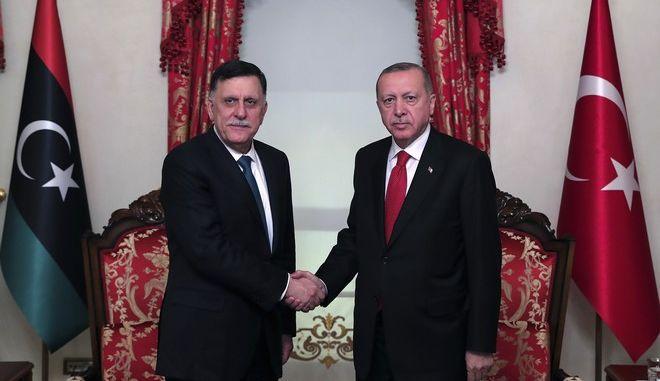 Από αριστερά ο επικεφαλής της διεθνώς αναγνωρισμένης κυβέρνησης της Λιβύης Φαγιέζ αλ Σαράι με τον Τούρκο πρόεδρο Ρετζέπ Ταγίπ Ερντογάν στη συνάντησή τους στην Κωνσταντινούπολη