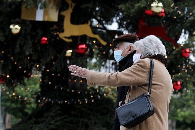 Ζευγάρι με μάσκες περπατά στη στολισμένη Αθήνα