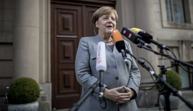 German Chancellor and chairwomen of the German Christian Democratic Union party  (CDU), Angela Merkel, addresses the media as she arrives for exploratory talks on a coalition between the CDU, the Christian Social Union party  (CSU), the German Free Democratic Party (FDP) and the Green Party in Berlin, Germany, Friday, Nov. 3, 2017. (Michael Kappeler/dpa via AP)