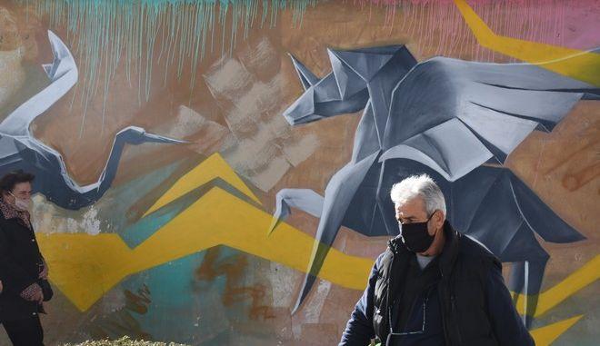 Πολίτης με μάσκα περπατά στην πόλη κατά τη διάρκεια του lockdown