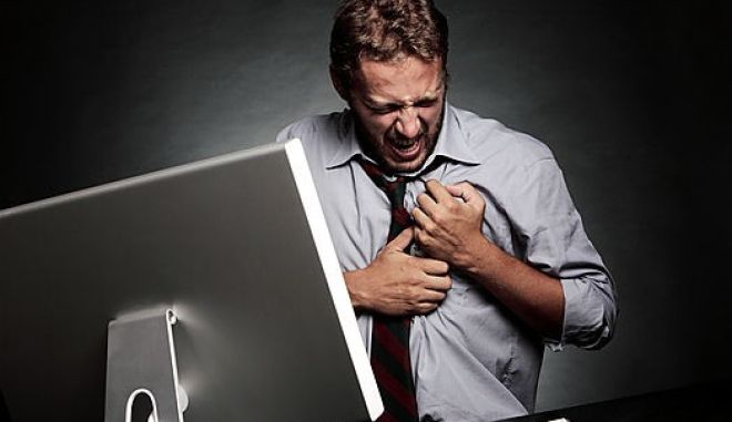 MODEL RELEASED. Stress-related heart attack. Man having a heart attack whilst working at a computer.