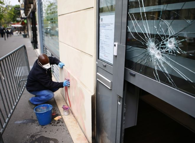A worker removes a graffiti outside French far-right presidential candidate Marine Le Pen's campaign headquarters, Thursday April 13, 2017 in Paris. The Paris fire department says no one was injured in the incident overnight and the blaze was quickly extinguished. The device hit an insurance office on the ground floor where Le Pen's campaign is based. (AP Photo/Francois Mori)