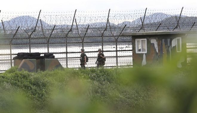 South Korean army soldiers patrol along the barbed-wire fence in South Korea's Paju, near the border with North Korea, Friday, Aug. 11, 2017. Military officials said Friday they plan to move ahead with large-scale U.S.-South Korea exercises later this month that North Korea, now finalizing plans to launch a salvo of missiles toward Guam, claims are a rehearsal for war. (AP Photo/Ahn Young-joon)