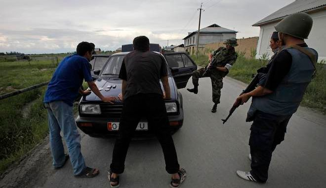 Kyrgyz soldiers and volunteers check passing cars and search passengers for weapons at a check point on the Uzbek border side of the outskirts of the southern Kyrgyz city of Osh in Kyrgyzstan,Wednesday, June 16, 2010. Heavy arms fire rang out over the Kyrgyz city of Osh before dawn Wednesday as authorities struggled to bring order to the country's south, which has been thrust into chaos by days of deadly ethnic riots. The violence has prompted more than 100,000 Uzbeks to flee for their lives to Uzbekistan, with tens of thousands more camped on the Kyrgyz side or stranded in a no man's land. (AP Photo/Alexander Zemlianichenko) ** zu unserem KORR **