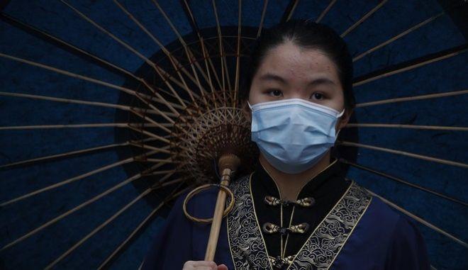 Κορονοϊός. Μια γυναίκα με μάσκα στο Πεκίνο