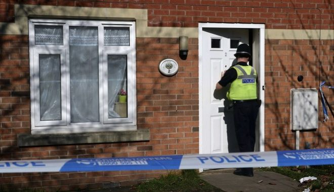 """A policeman enters a property on Navigation Way in Birmingham, England, Friday March 24, 2017. In a briefing outside Scotland Yard, London's top counterterror officer, Mark Rowley, said two more """"significant"""" arrests had been made, bringing to nine the number of people in custody over Wednesday's attack. Detectives have searched 21 properties in London, the central English city of Birmingham and Wales. (Joe Giddens/PA via AP)"""