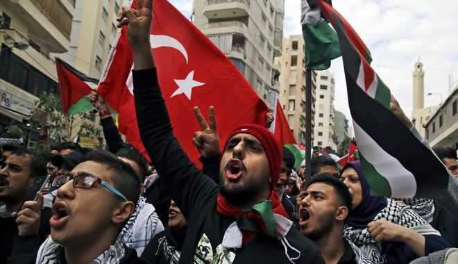 Protesters chant slogans as they hold Palestinian and a Turkish flags after Friday prayers during a march in the streets of Beirut, Lebanon, Friday, Dec. 8, 2017, against U S. President Donald Trump's decisions to recognize Jerusalem at the capital of Israel in Beirut. (AP Photo/Bilal Hussein)