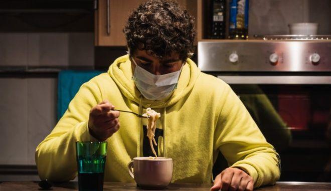 Άνθρωπος με μάσκα τρώει.