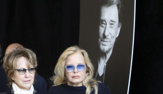 French singer Sylvie Vartan, right, and French actress Natalie Baye, both former wives of French rock star Johnny Hallyday, arrive at La Madeleine Church prior to Hallyday's funeral ceremony Saturday Dec. 9, 2017 in Paris. France is bidding farewell to its biggest rock star, honoring Johnny Hallyday with an exceptional funeral procession down the Champs-Elysees, a presidential speech and a parade of motorcyclists  all under intense security. (Ludovic Marin, Pool via AP)