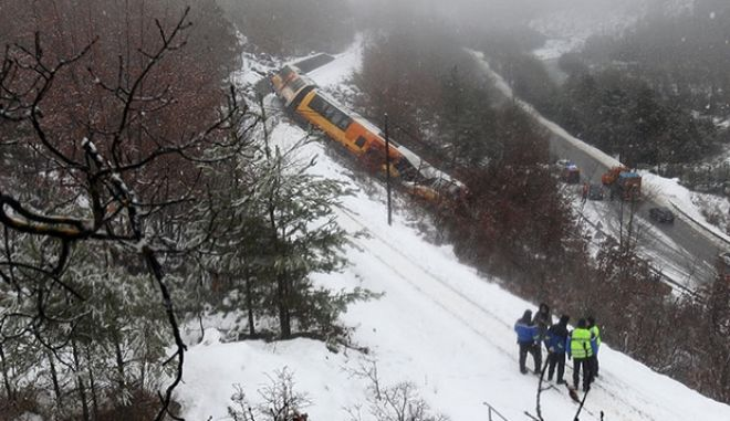 French gendarmes stand near the wreckage of a passenger train near Digne-les-Bains in the French Alps after it derailed on February 8, 2014. Two women were killed when a massive falling boulder hit a passing train in the French Alps on February 8, leaving one of its carriages dangling precariously off a steep, snow-covered embankment. Eight people were injured in the accident which took place as the train travelled from the coastal city of Nice to the popular tourist town of Digne-les-Bains along a narrow, winding, and sometimes breathtakingly steep track. AFP PHOTO / JEAN-CHRISTOPHE MAGNENET