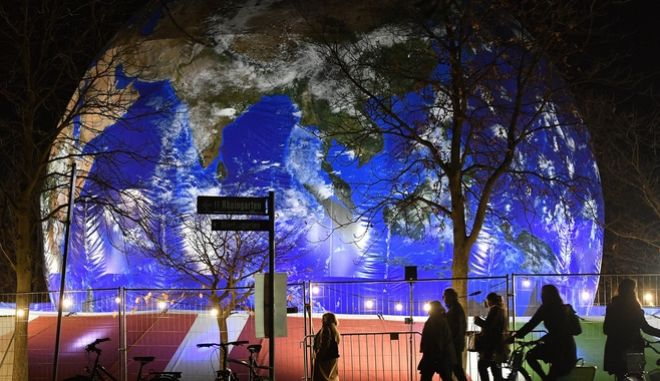 People pass the German pavilion in the shape of the earth during the COP 23 Fiji UN Climate Change Conference in Bonn, Germany, Wednesday evening, Nov. 15, 2017. (AP Photo/Martin Meissner)