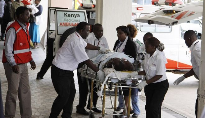 Doctors and medical staff help a man injured in the Mander attack at Kenyatta National Hospital in Nairobi, Kenya ,Tuesday July 7, 2015.  At least 14 people were killed in an attack early Tuesday in the country's north by al-Shabab, Islamic extremist rebels from neighboring Somalia, a Kenyan official said. Eleven people were also wounded in the attack which took place in Soko Mbuzi village in Mandera County near Kenya's border with Somalia, said Mandera County Commissioner Alex Nkoyo. (AP Photo/ Khalil Senosi)