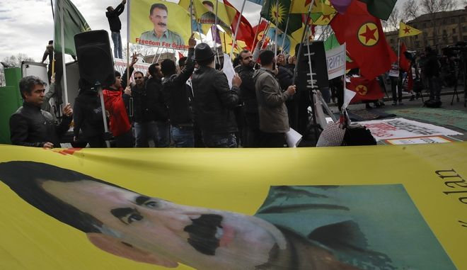 Demonstrators wave Turkish Workers' Party (PKK) flags bearing an image of PKK leader Abdullah Ocalan as they shout slogans during a sit-in near the Vatican in Rome, Monday, Feb. 5, 2018. Some 150 Kurdish protesters gathered near the Vatican on Monday as Turkish President Recip Tayyip Erdogan swept past in a long motorcade to the Vatican where he met with Pope Francis. (AP Photo/Alessandra Tarantino)