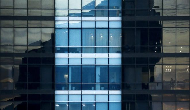 A woman stands watch on an office building as another building cast a shadow on it in Beijing, Tuesday, Sept. 26, 2017. The Asian Development Bank raised its growth forecast Tuesday for Asia's developing economies because global trade and conditions in the world's biggest economies are improving more than expected. (AP Photo/Andy Wong)