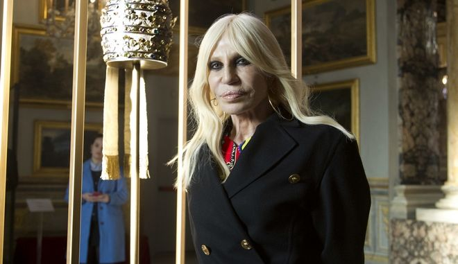 "Donatella Versace poses next to one of the Tiara (1877) of pope Pius IX in Rome, Monday, Feb. 26, 2018.  The Vatican is loaning some of its most beautiful liturgical vestments, jeweled miter caps and historic papal tiaras for an upcoming exhibit on Catholic influences in fashion at the Metropolitan Museum of Art. The Vatican culture minister, Cardinal Gianfranco Ravasi, joined Vogue Editor-in-Chief Anna Wintour and designer Donatella Versace in Rome on Monday to display a few of the Vatican treasures at the Palazzo Colonna, a onetime papal residence. ""Heavenly Bodies: Fashion and the Catholic Imagination"" is set to open May 10 at the Met's Costume Institute in New York. (AP Photo/Domenico Stinellis)"