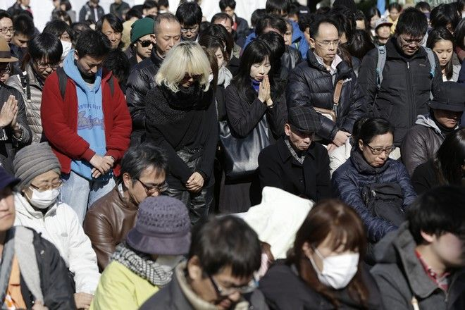 People mourn the victims of the March 11, 2011 earthquake and tsunami during a special memorial event in Tokyo, Saturday, March 11, 2017. Japan on Saturday marked the sixth anniversary of the 2011 tsunami that killed more than 18,000 people and left a devastated coastline along the country's northeast that has still not been fully rebuilt. (AP Photo/Eugene Hoshiko)
