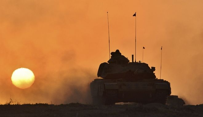 In this photo taken Friday, Sept. 29, 2017, a Turkish army tank moves, in Silopi, near the Habur border gate with Iraq, southeastern Turkey. Tanks with Turkish and Iraqi soldiers holding the Turkish and Iraqi flags rolled on a field as the two countries' militaries conducted joint exercises on Turkey's border with Iraq's semi-autonomous Kurdish region. (Pool photo via AP )