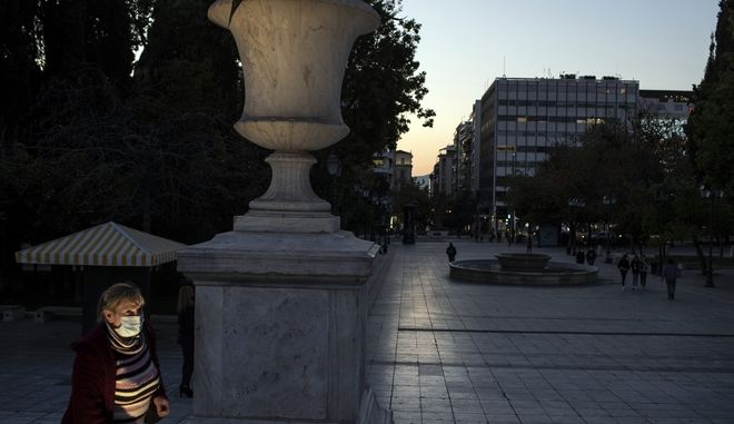 A woman wearing face mask to curb the spread of the coronavirus, walks at an empty Syntagma square, in central Athens, on Friday, Nov. 27, 2020. Greece's government spokesman on Thursday announced a weeklong extension to the country's current lockdown, due to the continued spread of the. COVID-19. (AP Photo/Petros Giannakouris)