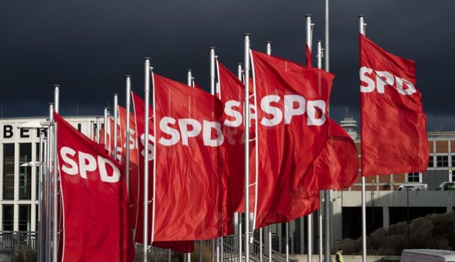 Flags of the Social Democratic Party, SPD, wave in the wind in front of the convention center of the party's convention in Berlin, Friday, Dec. 8, 2017. (AP Photo/Markus Schreiber)