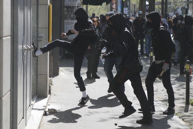 Κουκουλοφόροι κλοτσούν τη βιτρίνα ασφαλιστικής εταιρίας, κατά τη διάρκεια της γενικής απεργίας των εργαζομένων στους σιδηροδρόμους, στο Παρίσι. Χιλιάδες διαδηλωτές κατέβηκαν στους δρόμους σε μεγάλες πόλεις της Γαλλίας ενάντια στις μεταρρυθμίσεις Μακρόν