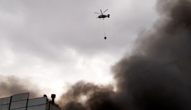 In this photo taken from a footage provided by the Russian Emergency Ministry Press Service, a Russian Emergency Situations Ministry helicopter dumps water on a large-scale fire at a warehouse in the village of Kanalstroi, 80 kilometers (50 miles) north of Moscow, Saturday, March 21, 2020. The fire covered an area of 60,000 square meters (37500 miles), no injuries have been reported. (Russian Emergency Ministry Press Service via AP)