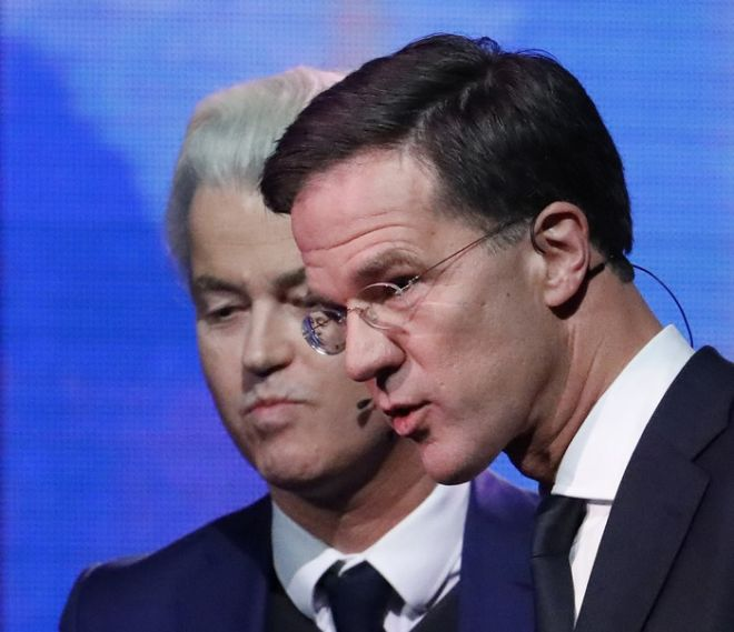 Right-wing populist leader Geert Wilders and Dutch Prime Minister Mark Rutte, right, leave the stage after a national televised debate, the first head-to-head meeting of the two political party leaders since the start of the election campaign, at Erasmus University in Rotterdam, Netherlands, Monday, March 13, 2017. (Yves Herman POOL via AP)