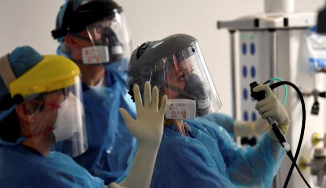 Μέλη του ιατρικού προσωπικού φροντίζουν έναν ασθενή με κορονοϊό σε νοσοκομείο της Αγγλίας.