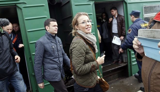 Russian socialite and TV host turned opposition activist Ksenia Sobchak, center, daughter of the late St. Petersburg mayor, Anatoly Sobchak, and opposition leader Ilya Yashin, left, leave the suburb train from Moscow to Khimki, Saturday Oct. 6, 2012, to support environmental activist and Khimki mayoral candidate Yevgenia Chirikova. Chirikova's campaign to lead the booming town of Khimki is seen as a test of the elect ability of the opposition and a sign of whether President Vladimir Putin is willing to tolerate dissent outside of the confines of the capital. The Kremlin has marginalised opposition figures, limiting access to media and painting them as big-city malcontents out of touch with the concerns of ordinary Russians.  (AP Photo/Sergey Ponomarev)
