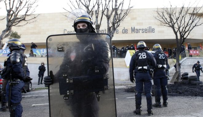 Riot police officers stand guard outside the Baumettes prison  as penitentiary staff block the entrance, in Marseille , southern France, Monday Jan. 22, 2018. Scores of unionized prison guards working at Europe's largest prison, Fleury-Mergois prison, along with others were demanding more security, more resources and safer handling of violent inmates. (AP Photo/Claude Paris)
