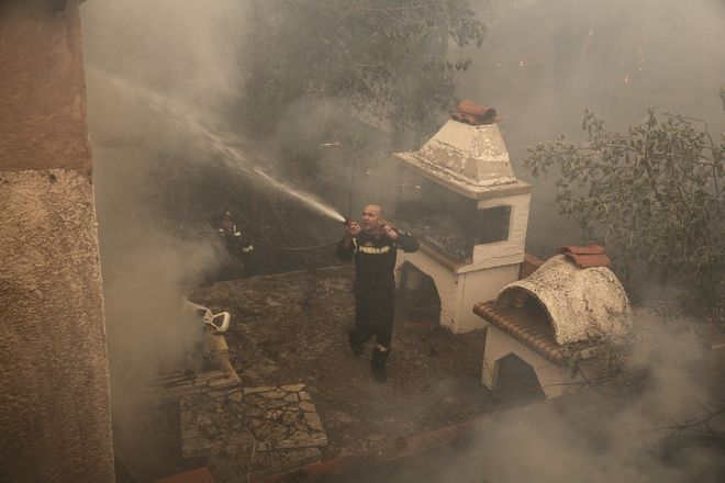 A firefighter sprays water inside the courtyard of a house during a forest fire at Kalamos village, north of Athens, Sunday, Aug. 13, 2017. A total of 53 wildfires broke out in Greece Saturday and more have done so Sunday, including at the beach resort of Kalamos near Athens. (AP Photo/Yorgos Karahalis)