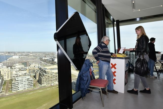 People casts their vote for the Dutch general election in a polling station on the twentieth floor of The A'dam Tower in Amsterdam, Netherlands, Wednesday, March 15, 2017. (AP Photo/Patrick Post)