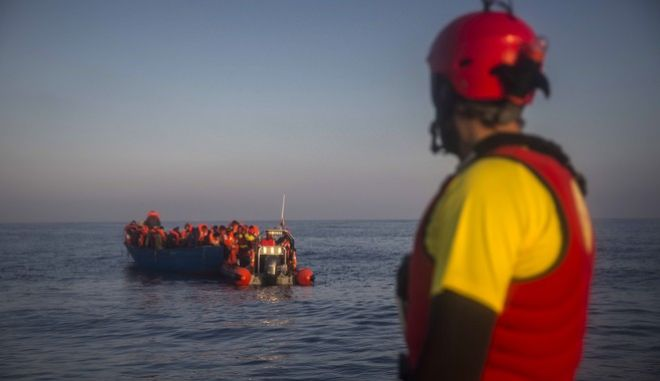 Members of the Spanish NGO Proactiva Open Arms assist refugees and migrants from different African and Asian countries, that left Libya aboard an overcrowded wooden boat trying to reach Europe, 14 miles North of Sabratha, Libya, early Thursday, March 2, 2017. (AP Photo/Santi Palacios)