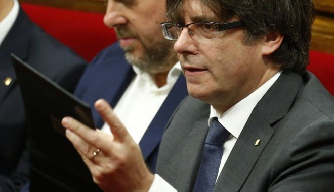 Catalonia regional President Carles Puigdemont, right, and Catalan regional Vice-President Oriol Junqueras attend a plenary session in Barcelona, Spain, Wednesday, Sept. 6, 2017. Catalan lawmakers are voting on a bill that will allow regional authorities to officially call an Oct. 1 referendum on a split from Spain, making concrete a years-long defiance of central authorities, who see the vote as illegal. (AP Photo/Manu Fernandez)