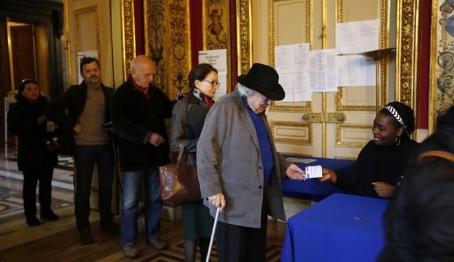 People line up to vote in the French presidential election at a polling station in Paris, France Sunday, May 7, 2017. Voters across France are choosing a new president in an unusually tense and important election that could decide Europe's future, making a stark choice between pro-business progressive Emmanuel Macron and far-right populist Marine Le Pen. (AP Photo/Emilio Morenatti)
