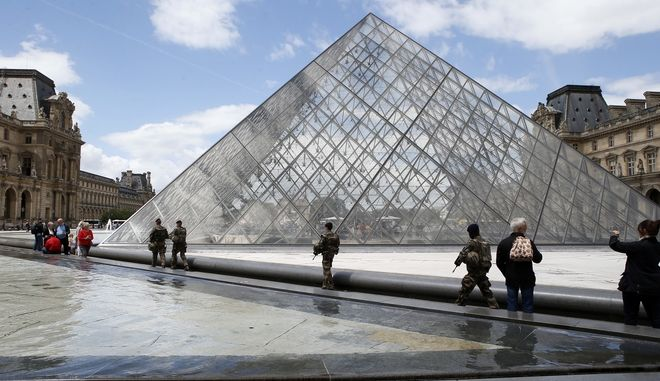 French soldiers patrol as tourists gather next the Pyramide of the Louvre Museum in Paris, France, Wednesday, June 7, 2017. (AP Photo/Francois Mori)