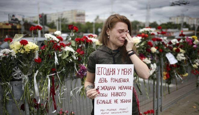 """Η Alina Krus, 26 ετών, κρατά μια αφίσα στο μέρος που πέθανε ένας διαδηλωτής, εν μέσω των συγκρούσεων στο Μινσκ, 12 Αυγούστου 2020 λέγοντας: """"Είναι τα γενέθλιά μου σήμερα. Έκανα μια ευχή να μην σκοτωθεί κανείς. Είμαστε ειρηνικοί άνθρωποι. Αρκετά με τη βία, σας παρακαλώ"""". Η Krus λέει ότι είναι η πρώτη της φορά που διαμαρτύρεται στο δρόμο - δεν μπορούσε να μείνει σπίτι και να γιορτάσει τα γενέθλιά της, ενώ ξέρει τόσα άτομα κρατούνται άδικα από τις αρχές."""