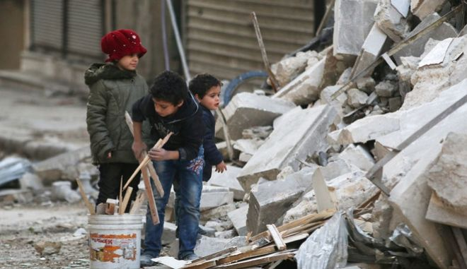 Children collect firewood amid damage and debris at a site hit yesterday by airstrikes in the rebel held al-Shaar neighbourhood of Aleppo, Syria November 17, 2016. REUTERS/Abdalrhman Ismail/File Photo