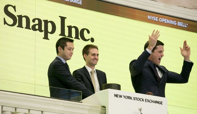 Snapchat co-founders Bobby Murphy, left, and CEO Evan Spiegel, ring the opening bell at the New York Stock Exchange while Thomas Farley, right, president of the Exchange, cheers on the crowd, as the company celebrates its IPO, Thursday, March 2, 2017. (AP Photo/Richard Drew)
