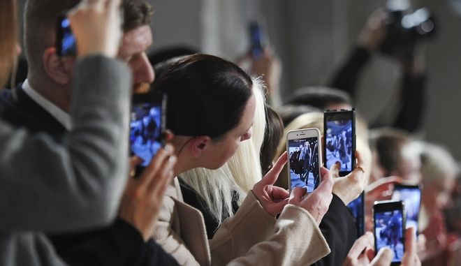 Spectators take pictures with their smartphones as they watch the the show of German designer Dorothee Schumacher at the Mercedes-Benz Fashion Week in Berlin, Tuesday, Jan. 17, 2017.  (Britta Pedersen/dpa via AP)