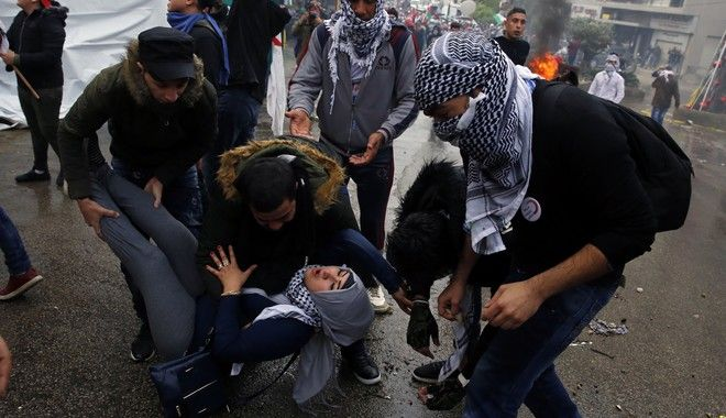 Protesters carry a girl who fainted after she inhaled tear gas fired by riot police during a demonstrations in front of the U.S. embassy in Aukar, east of Beirut, Lebanon, Sunday, Dec. 10, 2017.  A few hundred demonstrators, including Palestinians, pelted security outside the embassy with stones and burned an effigy of U.S. President Donald Trump in a protest to reject Washington's recognition of Jerusalem as capital of Israel. (AP Photo/Bilal Hussein)