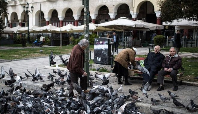 An elderly man feeds pigeons in Aristotle Square in Thessaloniki, Greece on March 20, 2015. /        ,  ,   20  2015.
