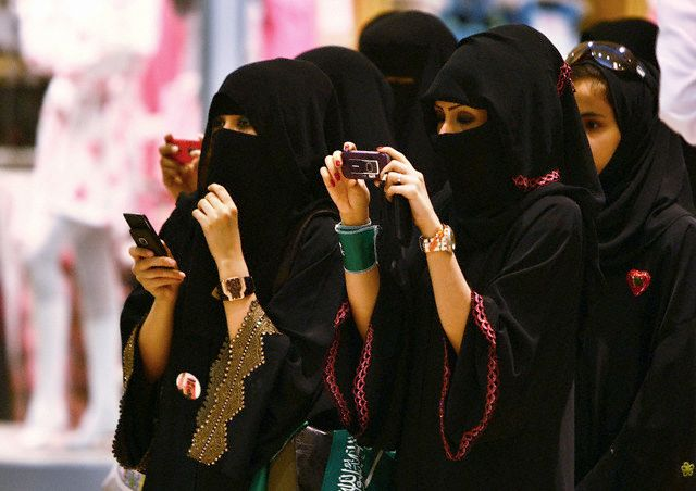 23 Sep 2009, RIYADH, Saudi Arabia --- Veiled Saudi women take photos of their children during a ceremony to celebrate Saudi Arabia's Independence Day in Riyadh September 23, 2009.  REUTERS/Fahad Shadeed  (SAUDI ARABIA SOCIETY ANNIVERSARY) --- Image by © FAHAD SHADEED/Reuters/Corbis