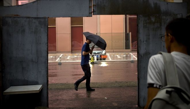 A man holds his umbrella against a gust of wind as he walks during a rain shower in Beijing, Friday, Aug. 11, 2017. Although China's capital is in a semi-dry climate, it receives much of its annual precipitation during the summer months. (AP Photo/Mark Schiefelbein)
