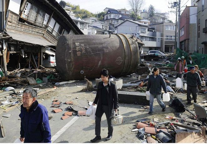 Photo Must Be Credited ©Alphafrance 69110609194706 09/06/2011 Combined photo shows local residents walking through debris on a street in Kesennuma, Miyagi Prefecture, to get water on March 14, 2011 ( top frame ), three days after the massive earthquake and tsunami struck the area, and the same area on June 3, 2011 ( bottom frame ). A large tank and a damaged house on the left side of the street have been cleared away.