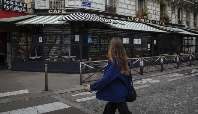 A woman walks by a closed cafe, in Paris, Tuesday Oct. 6, 2020. French authorities have placed the Paris region on maximum virus alert on Monday, banning festive gatherings and requiring all bars to close but allowing restaurants to remain open, as numbers of infections are rapidly increasing. (AP Photo/Lewis Joly)