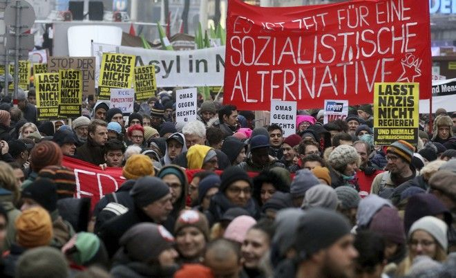 Protesters walk during a demonstration against the new Austrian government in Vienna Austria, Saturday, Jan. 13, 2018. (AP Photo/Ronald Zak)