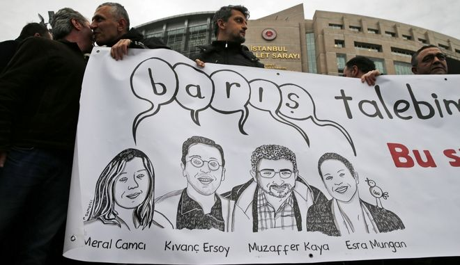 "People hold a banner showing some of the academics on trial and reads in Turkish: 'Peace', as they participate in a protest outside a court in Istanbul, Tuesday, Dec. 5, 2017, where Turkish academics went on trial for signing a declaration calling for end of hostilities in Turkey's southeast. A group of academics from universities in Istanbul are standing trial on charges of engaging in ""terrorist propaganda"" for signing a declaration calling for an end of hostilities against Kurdish rebels in Turkey's southeast. (AP Photo/Lefteris Pitarakis)"