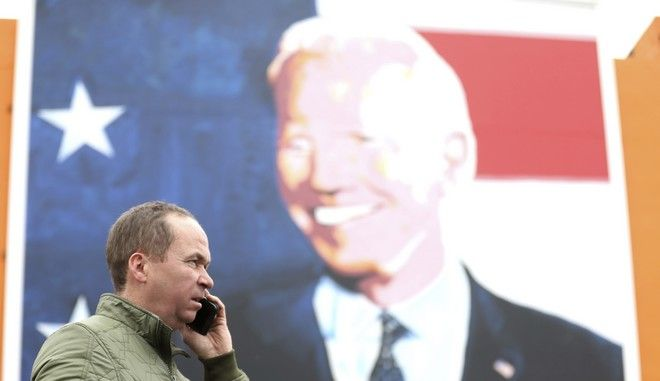Joe Blewitt a cousin of US Presidential candidate Joe Biden speaks on the phone beside a mural of Biden, in Ballina, west of Ireland, Wednesday, Nov. 4, 2020. Ballina is the ancestral home of US Presidential candidate Joe Biden. President Donald Trump and his Democratic challenger, Joe Biden, are in a tight battle for the White House.  (AP Photo/Peter Morrison)