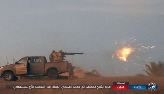 """This image posted online on Thursday, Sept. 28, 2017, by supporters of the Islamic State militant group on an anonymous photo sharing website, purports to show a gun-mounted vehicle operated by the group firing at Syrian troop in the eastern Syrian province of Deir el-Zour. The Arabic caption reads, """"The incursion of Sheikh Abu Mohammed al-Adnani may God give him mercy. Cover with fire to the brother who carried out martyrdom attack."""" (militant photo via AP)"""