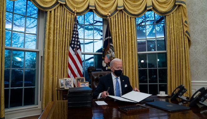Ο Πρόεδρος Τζο Μπάιντεν υπογράφει μια σειρά εκτελεστικών διαταγμάτων στο Οβάλ Γραφείο του Λευκού Οίκου, 20 Ιανουαρίου 2021.